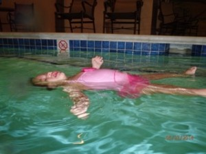 Girl floating in pink bathing suit